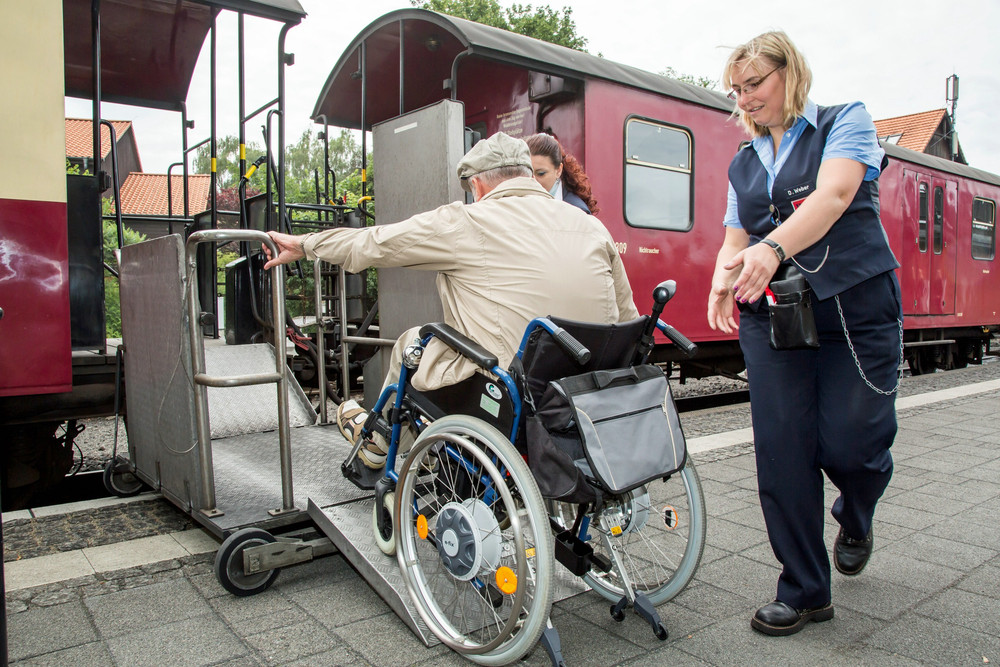 Schaffnerin hilft Rollstuhlfahrer auf Hubgerät