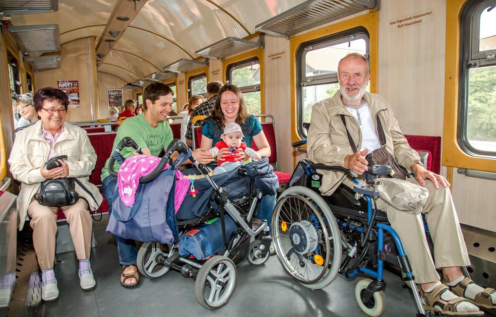 Personen mit Kinderwagen und Rollstuhl im Zug