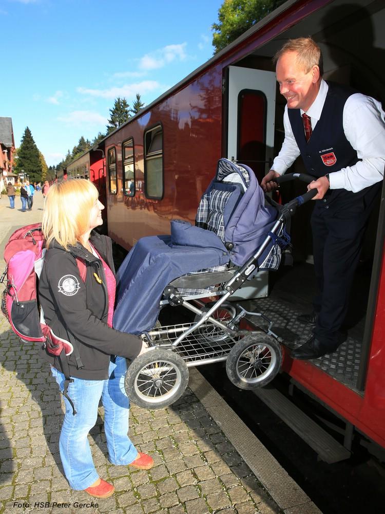 Schaffner hilft Frau mit Kinderwagen in Zug