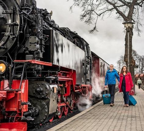 Personen mit Koffer vor Dampflok