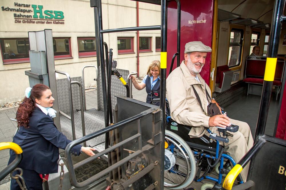 Schaffnerinnen helfen Rollstuhlfahrer auf Zug